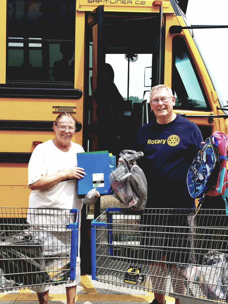 Presidents hard at work! Sunrise Club President Priscilla Scalf and Columbus Club President Roger Brinkman loading up the bus with supplies